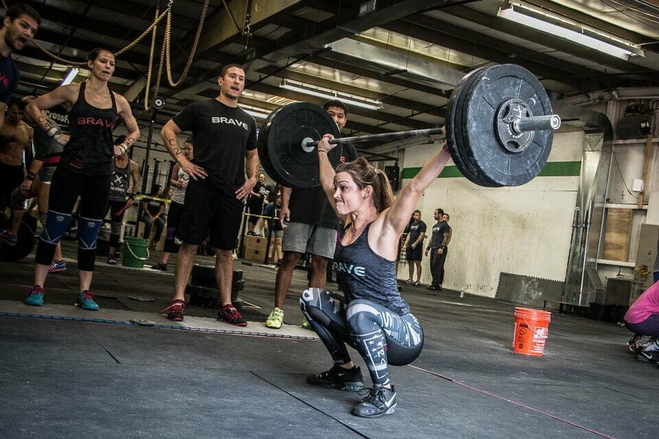 crossfit woman doing snatch olympic lift