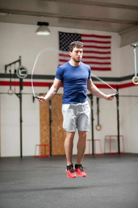 Fit athletic young man using a skipping rope to train in a crossfit gym jumping midair in a health and fitness concept