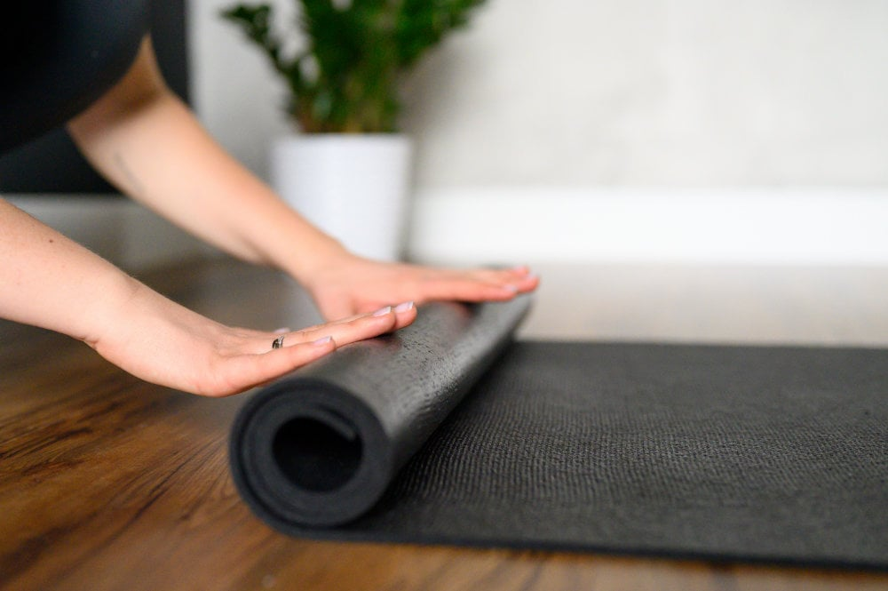 A Woman Rolls Up A Yoga Mat After A Workout In The Studio
