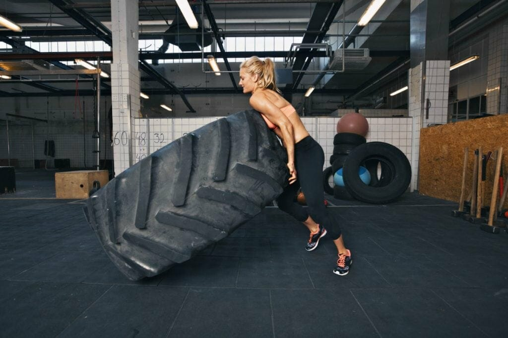 Fit Female Athlete Flipping A Huge Tire
