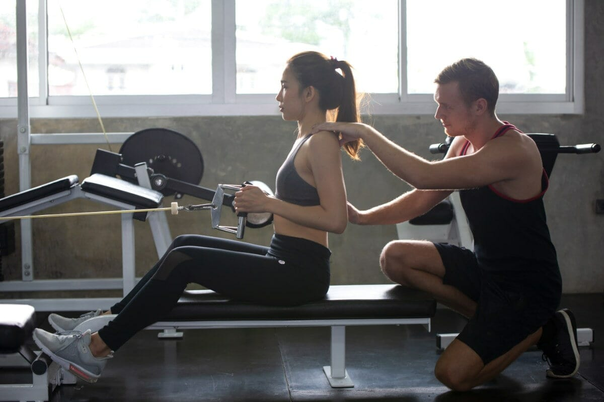 Personal Trainer With Client In Regular Gym