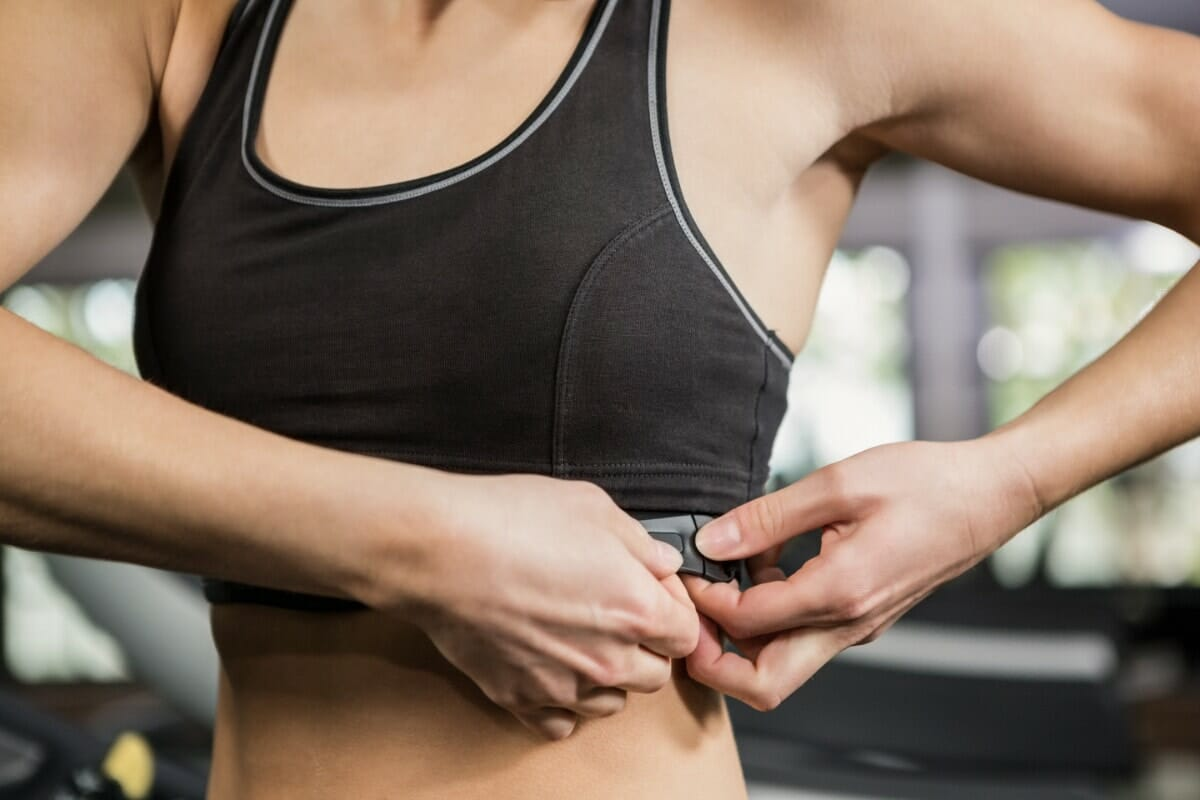 Mid Section Of Woman In Gym Wearing Heart Rate Monitor Around Her Chest