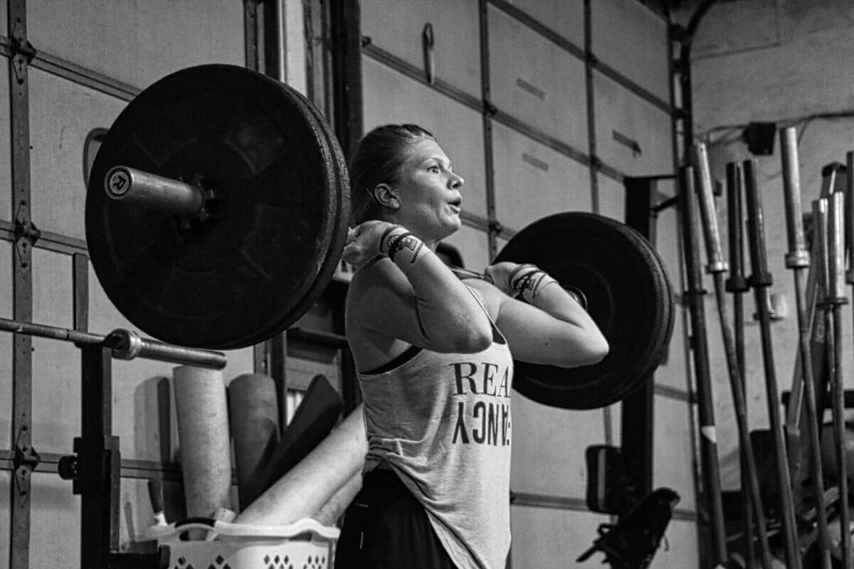 Female Crossfit Athlete Performing Clean With Wrist Straps